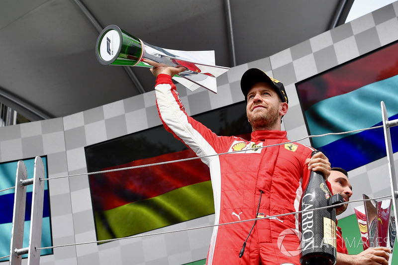 Race winner Sebastian Vettel, Ferrari celebrates with the trophy on the podium