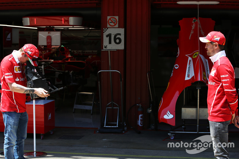 Kimi Raikkonen, Ferrari, takes a picture of Sebastian Vettel, Ferrari on a vintage camera in the pits