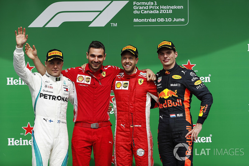 Sebastian Vettel, Ferrari, celebrates victory on the podium with Valtteri Bottas, Mercedes AMG F1 an