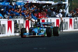 Michael Schumacher, Benetton B194, celebra con el equipo de Benetton mientras cruza la línea de meta
