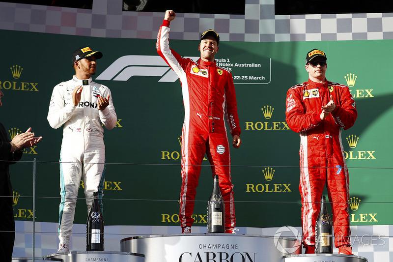 Sebastian Vettel, Ferrari, celebrates victory on the podium with second place Lewis Hamilton, Merced