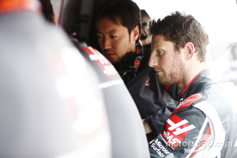 Romain Grosjean, Haas F1 Team, joins colleagues on the pit wall