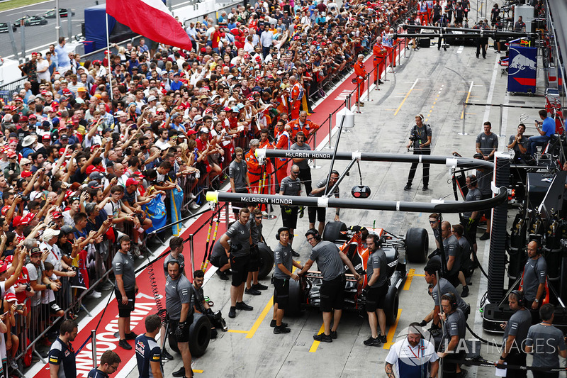 Fans watch the McLaren team at work