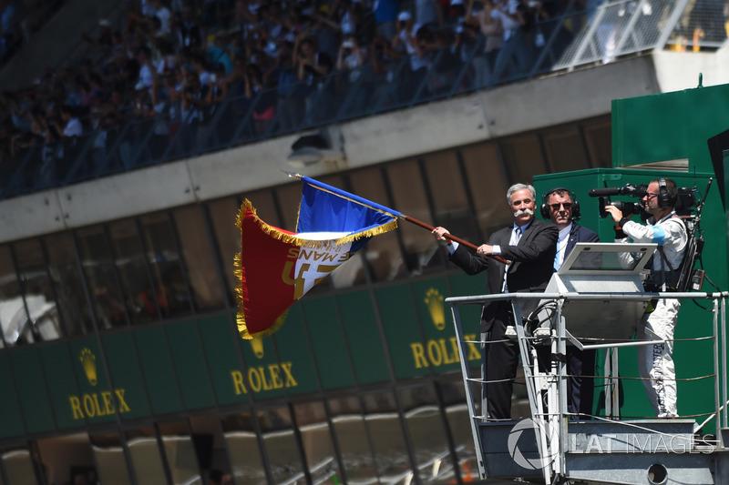 Chase Carey agita la bandera francesa para dar el inicio de la carrera