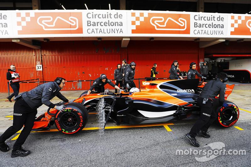 Los miembros del equipo McLaren empujan el McLaren MCL32 de Fernando Alonso, McLaren, al pit lane