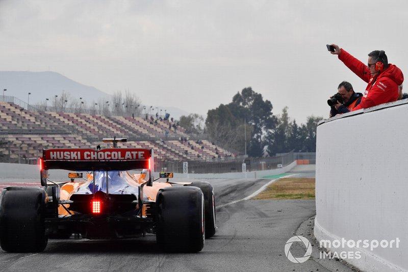 Ferrari personnel photographs Lando Norris, McLaren MCL34 at the end of pit lane