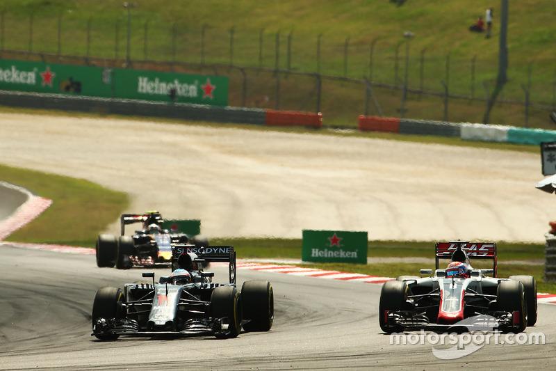 (L to R): Fernando Alonso, McLaren MP4-31 and Romain Grosjean, Haas F1 Team VF-16 battle for position