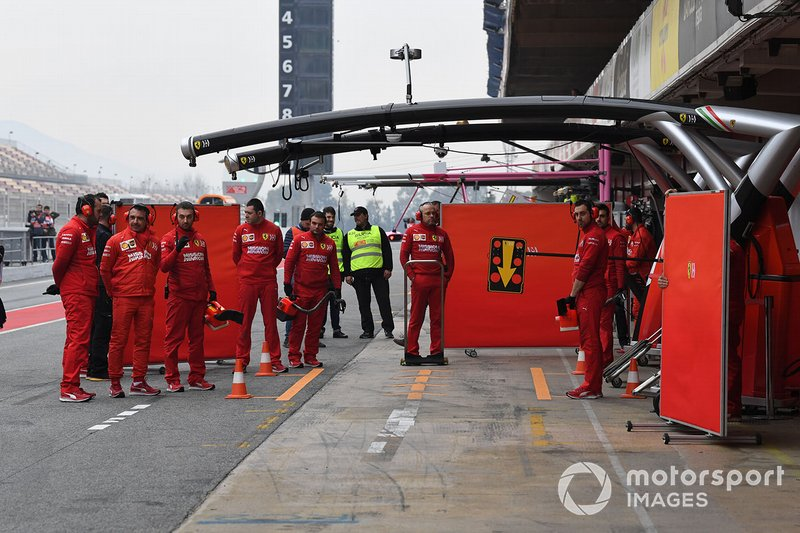 The Ferrari team wait for the return of their car in the pit lane