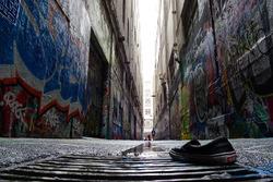 A Vans trainer in an alleyway