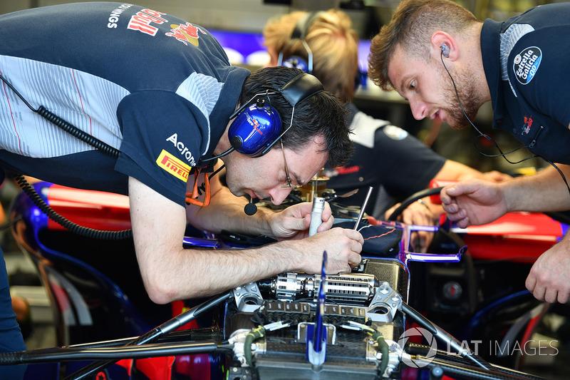 Mecánicos de la Scuderia Toro Rosso STR12 miran la nariz del Scuderia Toro Rosso STR12