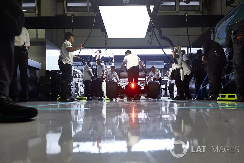 Engineers return a Mercedes AMG F1 W09 to their garage