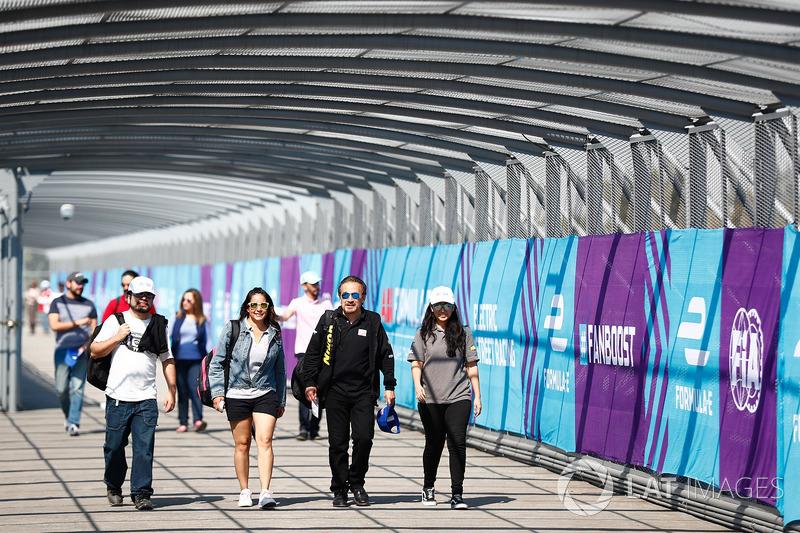 Spectators walk along the over track bridge