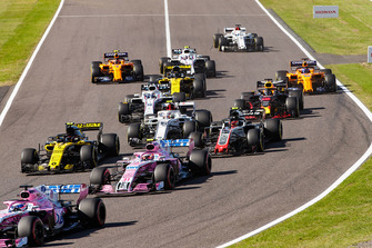 Sergio Perez, Racing Point Force India VJM11, leads Esteban Ocon, Racing Point Force India VJM11, Carlos Sainz Jr., Renault Sport F1 Team R.S. 18, Kevin Magnussen, Haas F1 Team VF-18, Charles Leclerc, Sauber C37, and the remainder of the field at the start