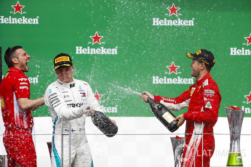Valtteri Bottas, Mercedes AMG F1, y Sebastian Vettel, Ferrari, celebran en el podio