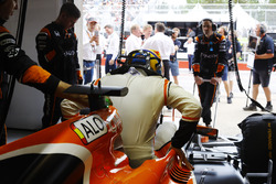 Fernando Alonso, McLaren, enters his cockpit in the garage
