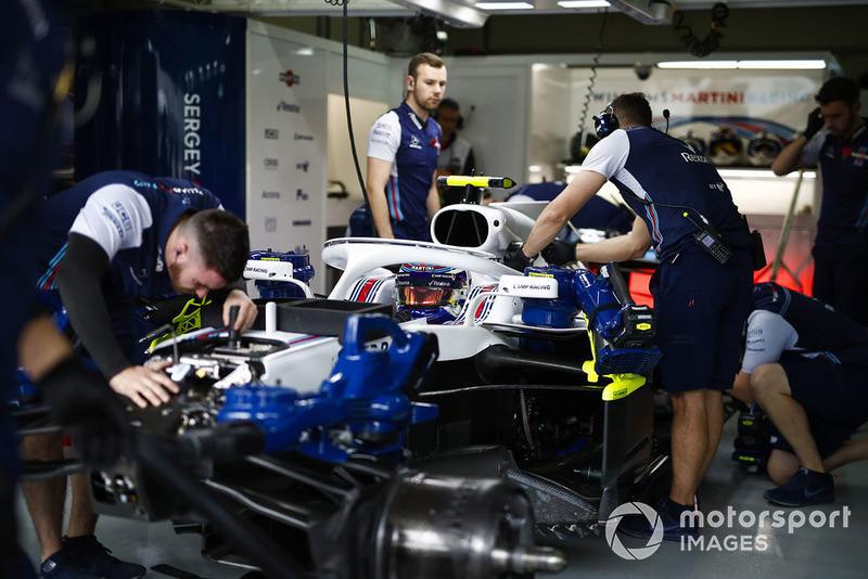 Les mécaniciens sur la voiture de Sergey Sirotkin Williams FW41 dans le garage