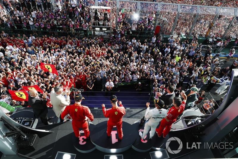 Sebastian Vettel, Ferrari, celebrates victory on the podium with Lewis Hamilton, Mercedes AMG F1, and Kimi Raikkonen, Ferrari