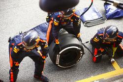 Los mecánicos de Red Bull esperan fuera de su garaje con un neumático Pirelli
