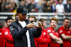 Lewis Hamilton, Mercedes AMG F1, takes a picture of junior garters