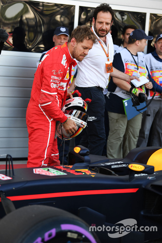 Sebastian Vettel, Ferrari looks at the Red Bull Racing RB13 in parc ferme