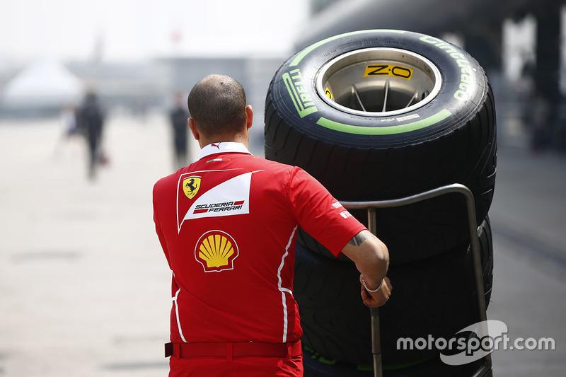 A Ferrari team members pushes a stack of Pirelli tyres