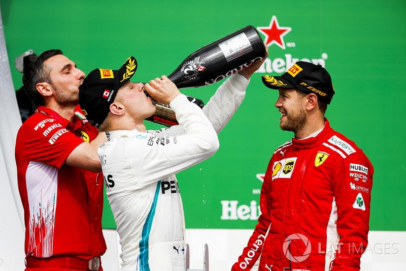 Valtteri Bottas, Mercedes AMG F1, 2nd position, drinks Champagne on the podium alongside Nicola Bariselli, Race Engineer, Ferrari, as Sebastian Vettel, Ferrari, 1st position, looks on