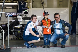 A Williams team member poses for a picture with a young fan in front of the team's garage
