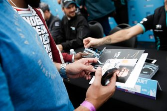 A fan collecting signed driver cards at the autograph session