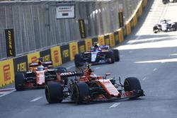 Stoffel Vandoorne, McLaren MCL32, leads Fernando Alonso, McLaren MCL32, and Carlos Sainz Jr., Scuderia Toro Rosso STR12
