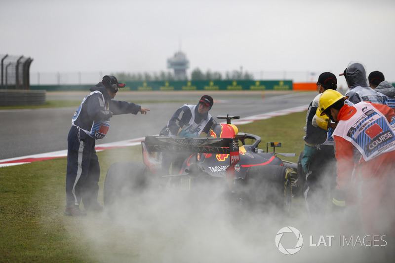 Marshals use fire extinguishers on the Daniel Ricciardo Red Bull Racing RB14 Tag Heuer