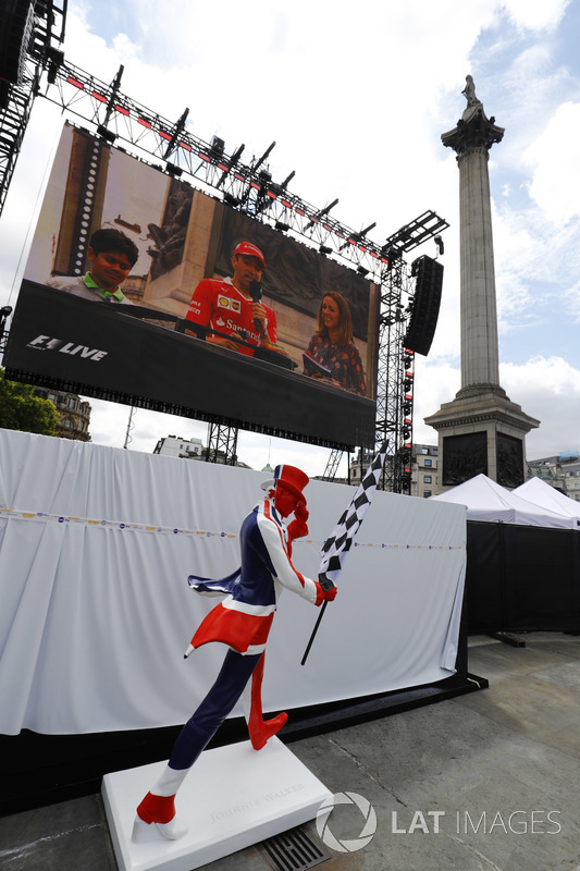 Union flag painted living statue in front of a big screen