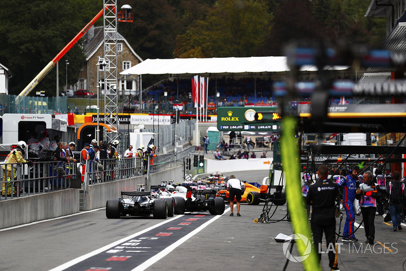 Valtteri Bottas, Mercedes AMG F1 W09, Kevin Magnussen, Haas F1 Team VF-18, Romain Grosjean, Haas F1 Team VF-18, and Brendon Hartley, Toro Rosso STR13, form the rear of a queue of cars in the pit lane, as FP3 is restarted following a red flag incident for a crash involving Stoffel Vandoorne, McLaren MCL33. Photographer Romano Poli can be seen on the right