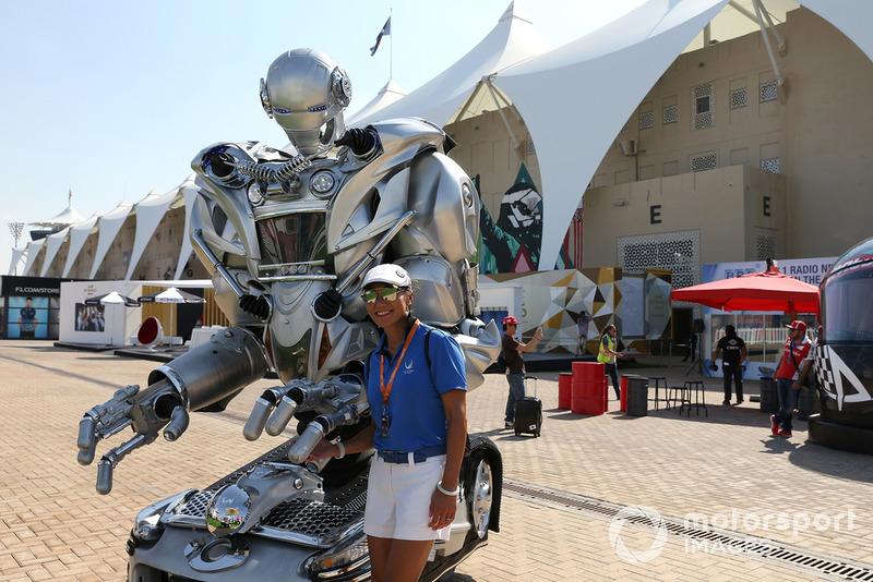 Una tifosa in posa accanto a un robot