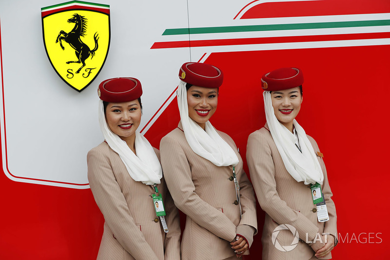 Emirates stewardesses pose next to the Prancing Horse of Ferrari