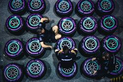 Mecánicos de Mercedes sentados sobre neumáticos Pirelli