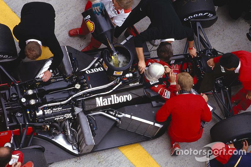 Alain Prost dans sa McLaren MP4/3 TAG Porsche pendant que les mécaniciens travaillent sur la voiture et la ravitaillent en essence