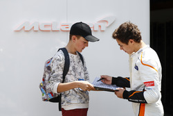 Lando Norris, McLaren, signs an autograph for a fan