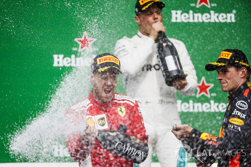Valtteri Bottas, Mercedes AMG F1, 2nd position, Sebastian Vettel, Ferrari, 1st position, and Max Verstappen, Red Bull Racing, 3rd position, celebrate with Champagne on the podium