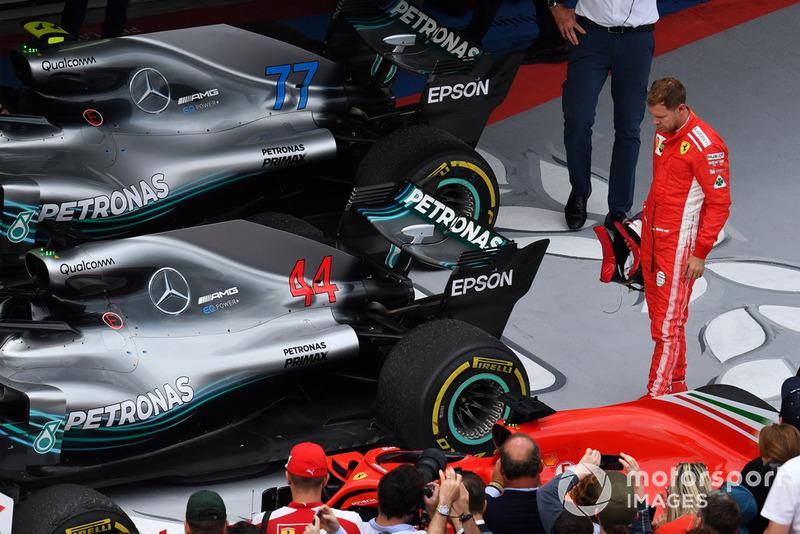 Sebastian Vettel, Ferrari looks at the rear Pirelli tyre of the car of Lewis Hamilton, Mercedes-AMG F1 W09 in parc ferme