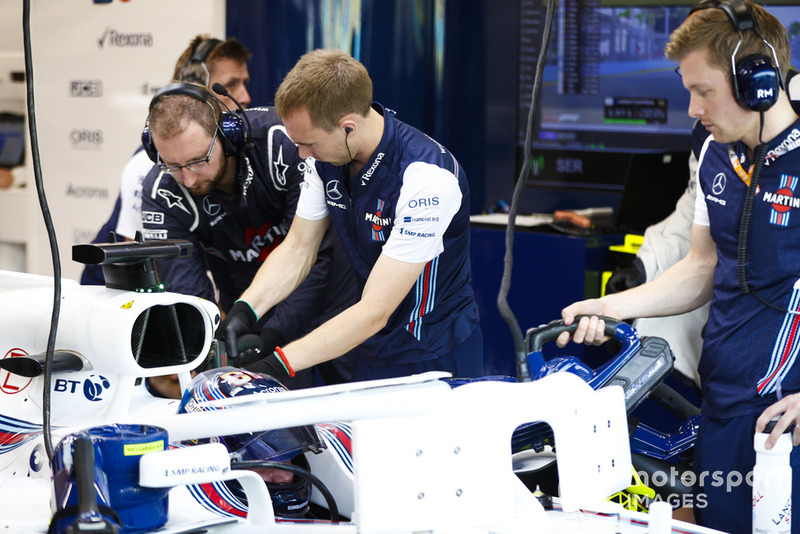 Engineers work on the car of Lance Stroll, Williams FW41, in the garage