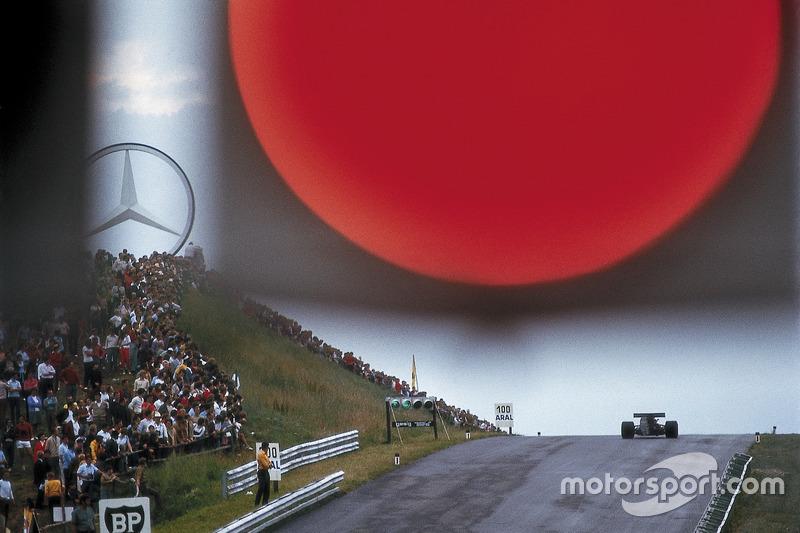 """Un coche solitario subiendo la colina de Zeltweg directamente bajo un rojo """"sol"""", el signa de pitlane"""