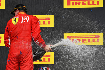 Race Winner Kimi Raikkonen, Ferrari celebrates with the champagne on the podium with the trophy
