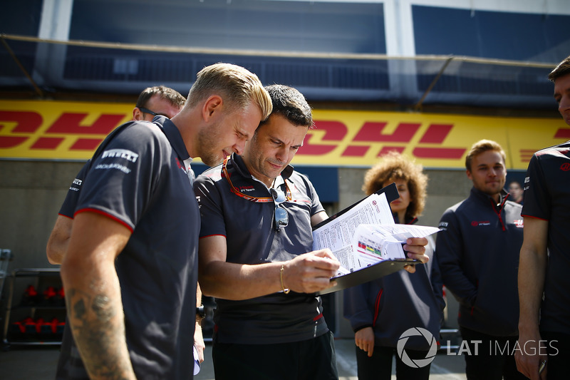 Kevin Magnussen, Haas F1 Team, views a document with engineer Guiliano Salvi