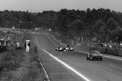 Roger Masson, Pierre Monneret, Rene Bonnet Aerodjet LM6 Renault, lies upside down in the middle of the road as the Bruno Basini, Robert Bouharde, Rene Bonnet Aerodjet LM6 Renault, approaches