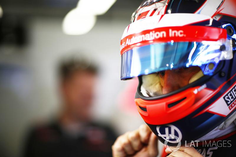 Romain Grosjean, Haas F1 Team, puts on his helmet in the garage