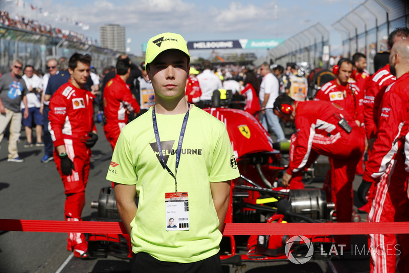 A Grid Kid stands in front of a Ferrari