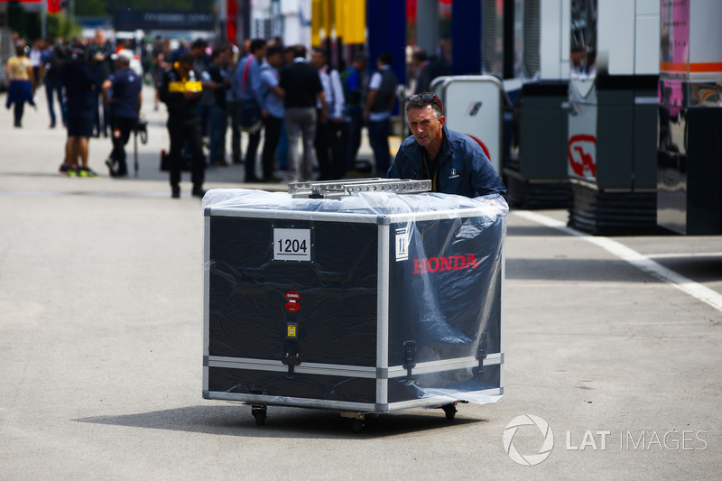 Un miembro del equipo de Honda empuja una caja de motor en el paddock