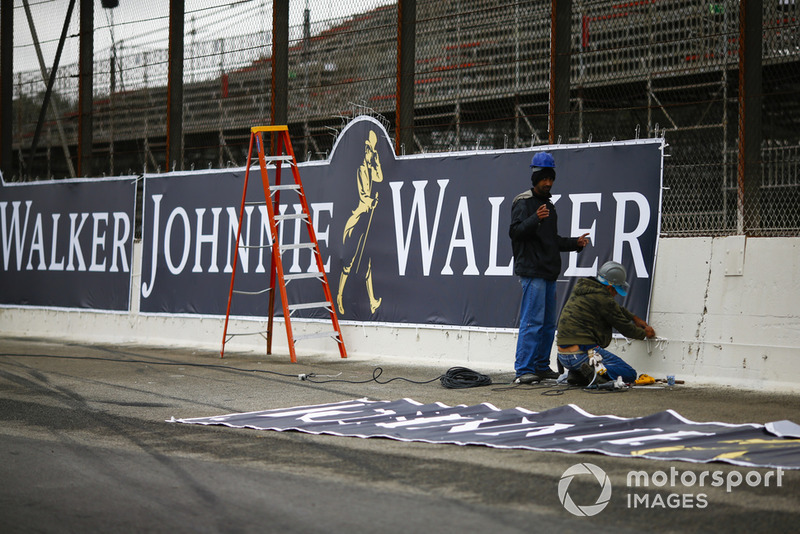 Les travailleurs du circuit terminent de placer les panneaux publicitaires