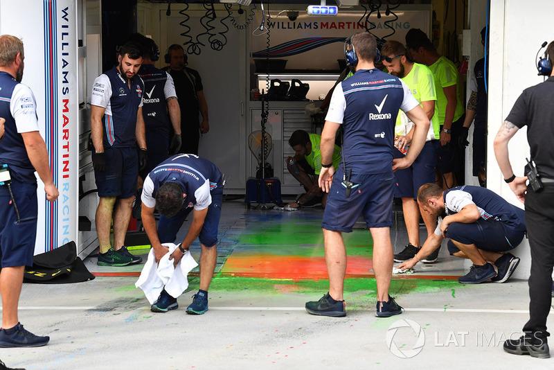 Los mecánicos de Williams limpian la parafina aerodinámica del piso del garaje