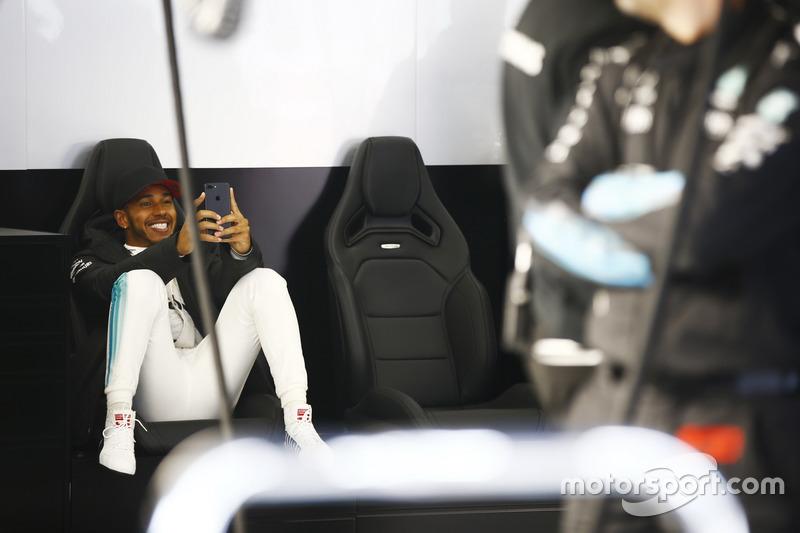 Lewis Hamilton, Mercedes AMG, avec son téléphone dans le garage